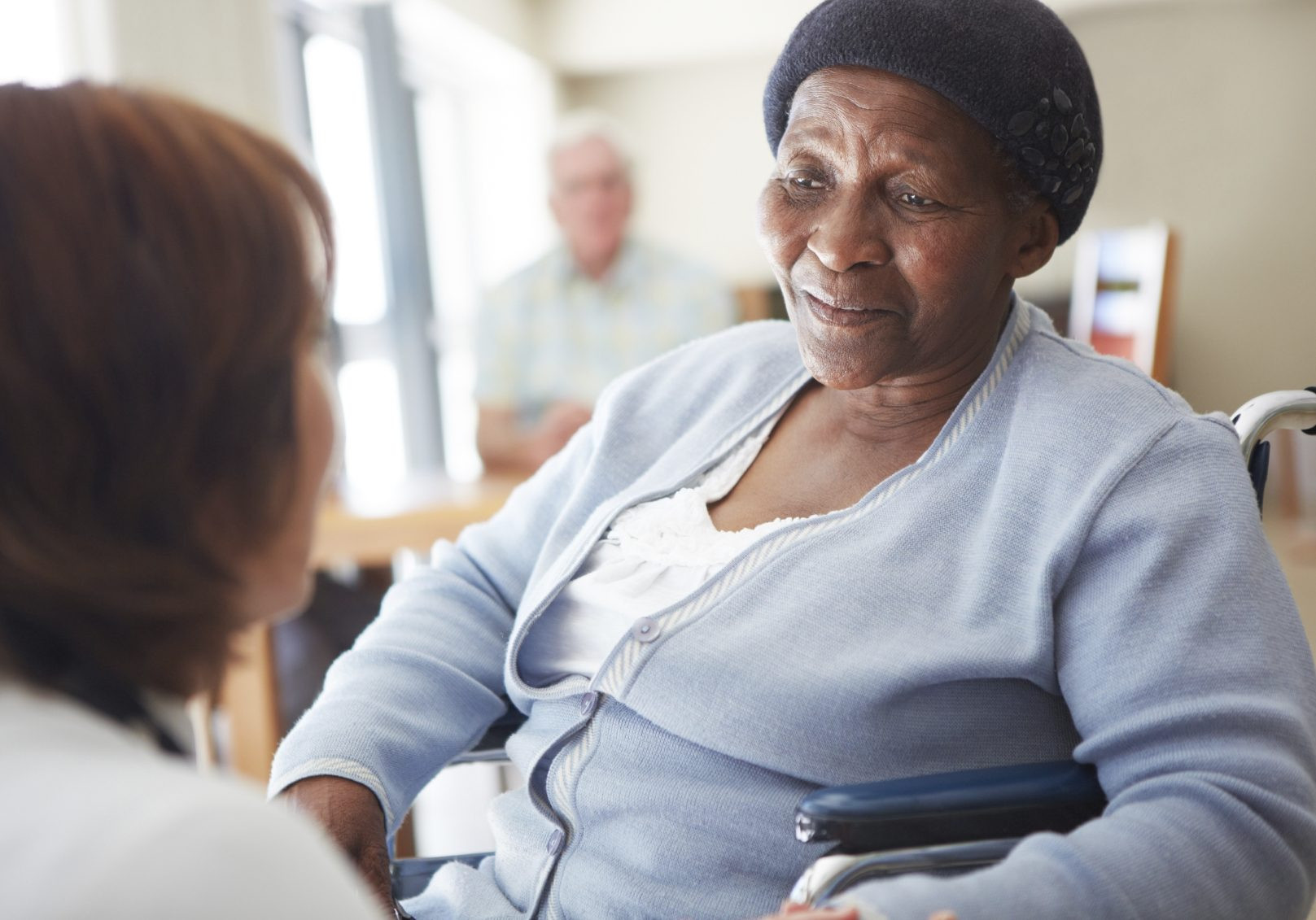 A caregiver talking to a wheelchair-bound patient